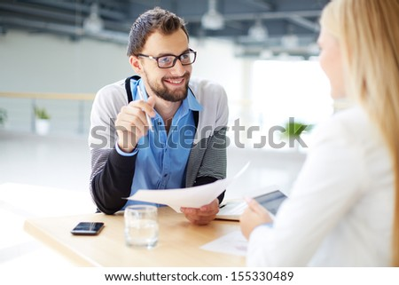 Smiling businessman with paper talking to his colleague at meeting  - stock photo
