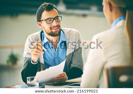 Smiling businessman with papers consulting his colleague at meeting  - stock photo