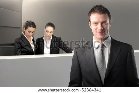 Smiling businessman with receptionists on the background