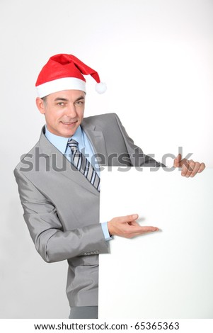 Smiling businessman with Santa hat showing white board
