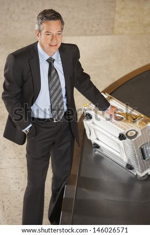 Smiling businessman with suitcase at luggage carousel in airport - stock photo