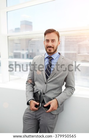 Smiling businessman with touch pad and mobile phone in hands standing in office interior after successful signing the contract, cheerful male manager holding portable digital tablet and cell telephone