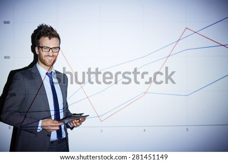 Smiling businessman with touchpad standing by wall with graph