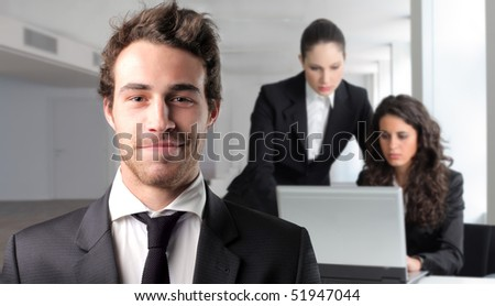 Smiling businessman with two businesswoman working on the background - stock photo