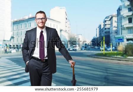 smiling businessman with umbrella and city background - stock photo