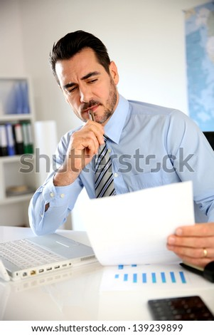 Smiling businessman working in office - stock photo