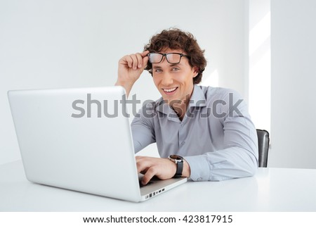 Smiling businessman working on laptop computer and looking at camera in office