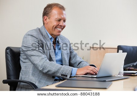 Smiling businessman working on laptop in an office - stock photo