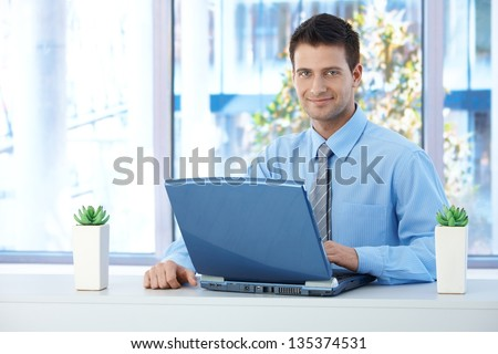 Smiling businessman working on laptop in office, looking at camera confidently. - stock photo