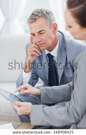 Smiling businessman working with his colleague in bright office - stock photo