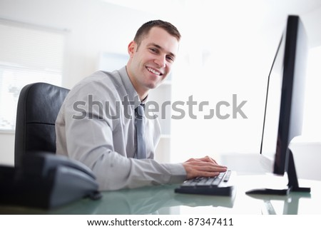Smiling businessman working with his computer - stock photo