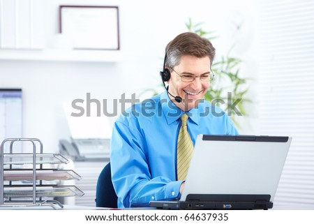 Smiling  businessman working with laptop and headset - stock photo