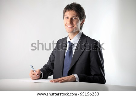 Smiling businessman writing a document - stock photo