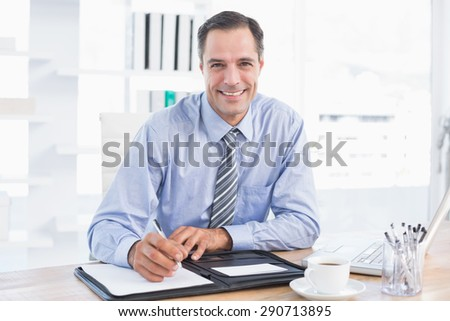 Smiling businessman writing on a paper in his office