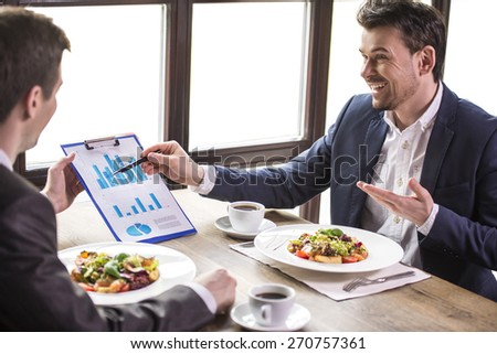Smiling businessmen analyzing graphs during a business lunch. - stock photo