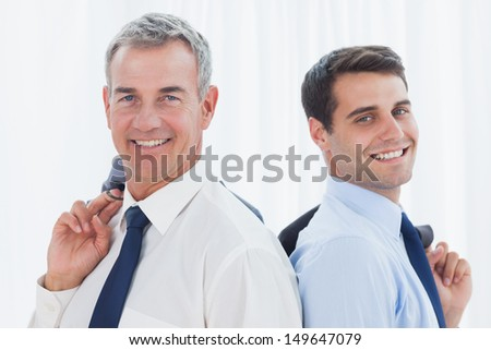 Smiling businessmen in bright office posing back to back together while holding their jacket