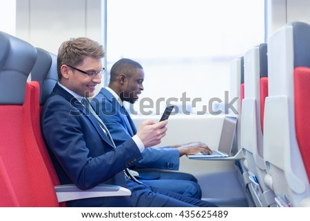 Smiling businessmes in a train - stock photo