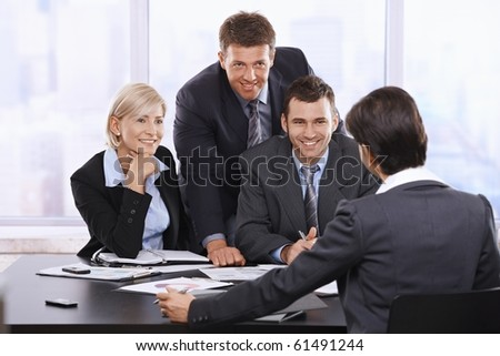 Smiling businesspeople at meeting looking at executive in office.?