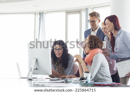 Smiling businesspeople working together at conference table - stock photo
