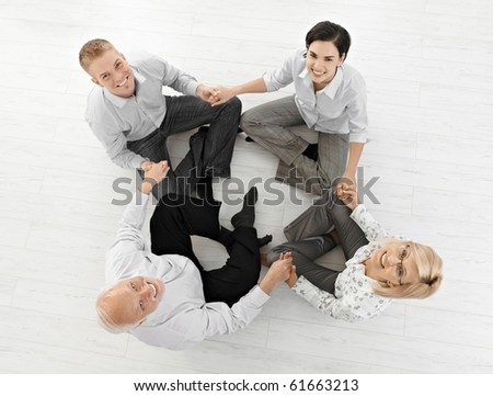 Smiling businessteam doing relaxation, looking at camera sitting on floor in lotus posture, high angle view.? - stock photo