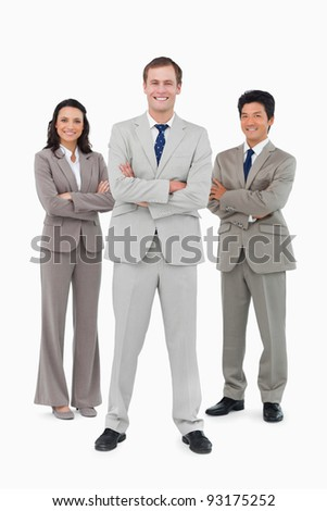 Smiling businessteam with folded arms against a white background