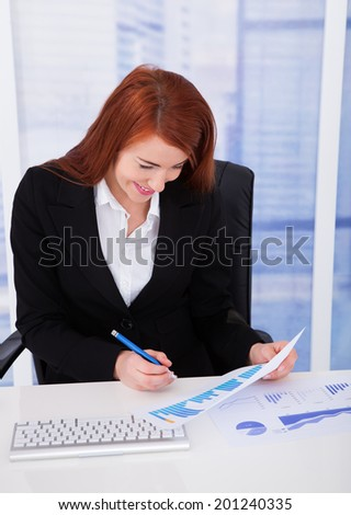 Smiling businesswoman analyzing graph at desk in office