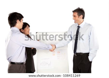 Smiling businesswoman and businessman shaking hand at presentation in office.