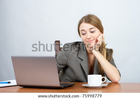 Smiling businesswoman at desk with hand on face, looking to the laptop screen - stock photo