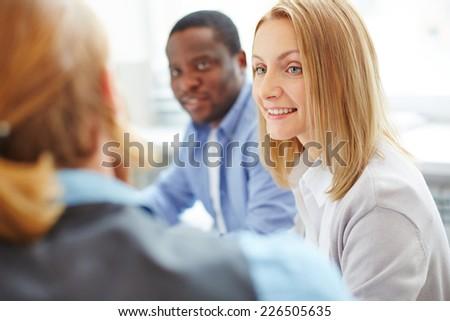 Smiling businesswoman between her co-workers - stock photo