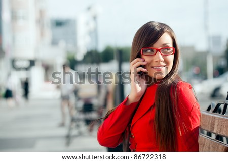 smiling businesswoman  calling by phone, wearing red glasses - stock photo