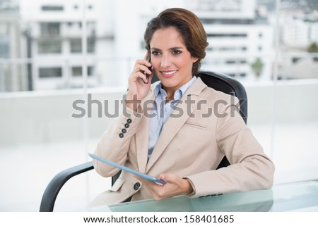 Smiling businesswoman calling with smartphone in bright office - stock photo