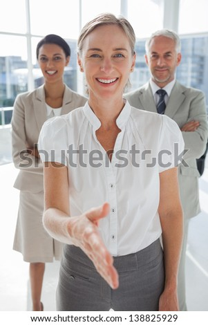 Smiling businesswoman giving a handshake with colleagues behind standing together - stock photo