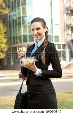 smiling businesswoman going to work with coffee and donut , outdoor - stock photo