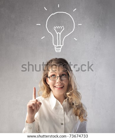 Smiling businesswoman having an idea with light bulb over her head - stock photo