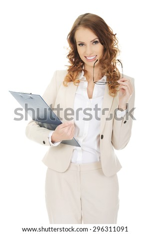 Smiling businesswoman holding a clipboard. - stock photo