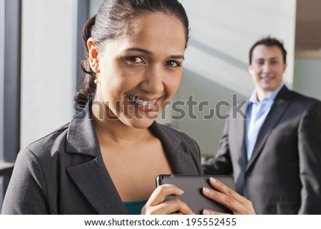 Smiling businesswoman holding a tablet while meeting with businessman in modern office building - stock photo