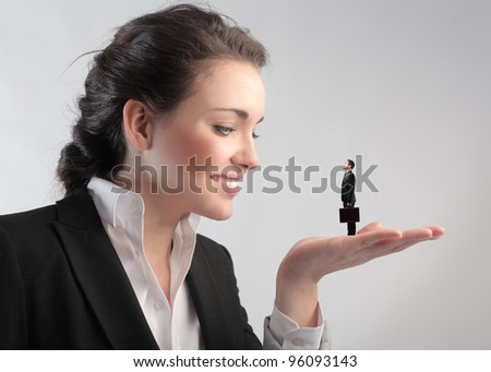 Smiling businesswoman holding a tiny businessman in her hand - stock photo