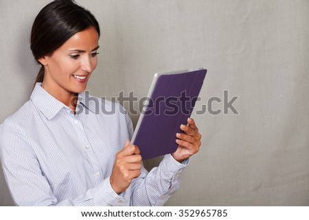 Smiling businesswoman holding and reading tablet in formalwear on grey texture background
