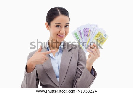 Smiling businesswoman holding bank notes against a white background