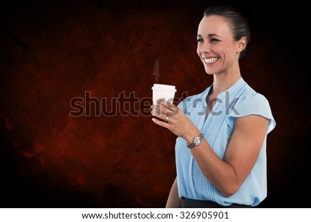 Smiling businesswoman holding disposable cup against dark background