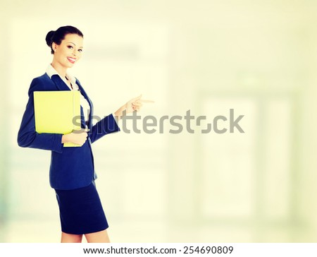 Smiling businesswoman holding files and pointing.