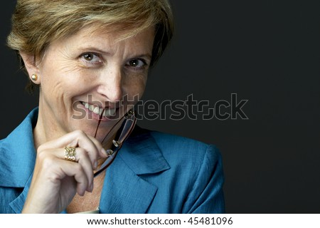 Smiling businesswoman holding glasses, portrait. - stock photo
