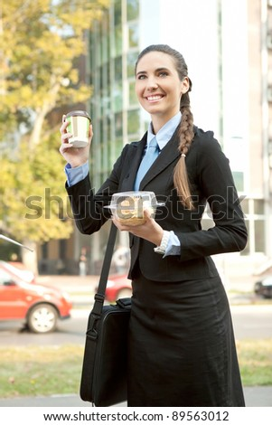 smiling businesswoman holding her  breakfast