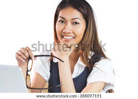 Smiling businesswoman holding her chin and her eyeglasses on white background - stock photo