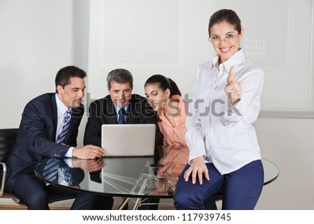 Smiling businesswoman holding her thumbs up with team in the background - stock photo