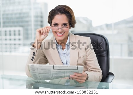 Smiling businesswoman holding newspaper at her desk in bright office - stock photo