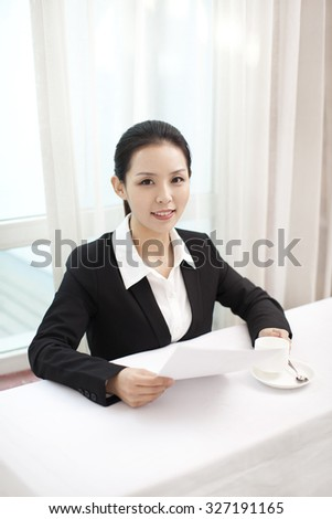 Smiling businesswoman holding paper in an office