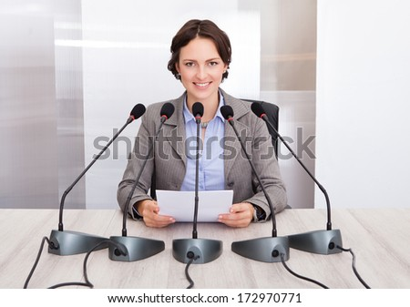 Smiling Businesswoman Holding Paper Speaking In Front Of Multiple Microphones - stock photo