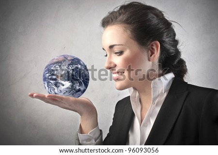 "Smiling businesswoman holding the Earth in her hand ""Elements of this image furnished by NASA"" - stock photo"