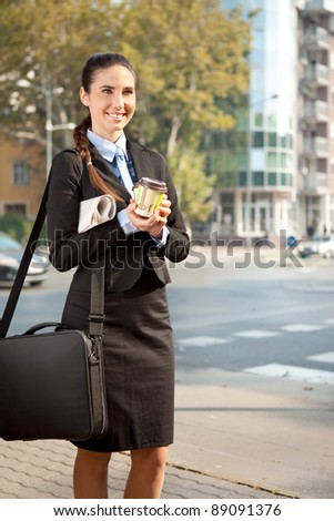smiling businesswoman holding two cup of coffee, standing on street - stock photo